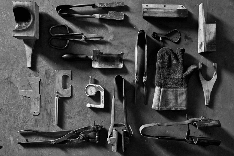 A photo of the very basic tools used by glassmakers, including scissors, a  compass, and wooden paddle.