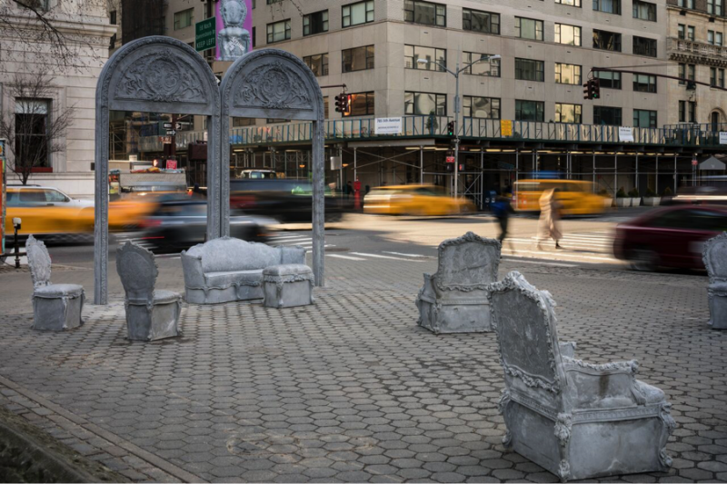 Concrete furniture and arches created by artist Liz Glynn sit in a cobblestone plaza in New York.
