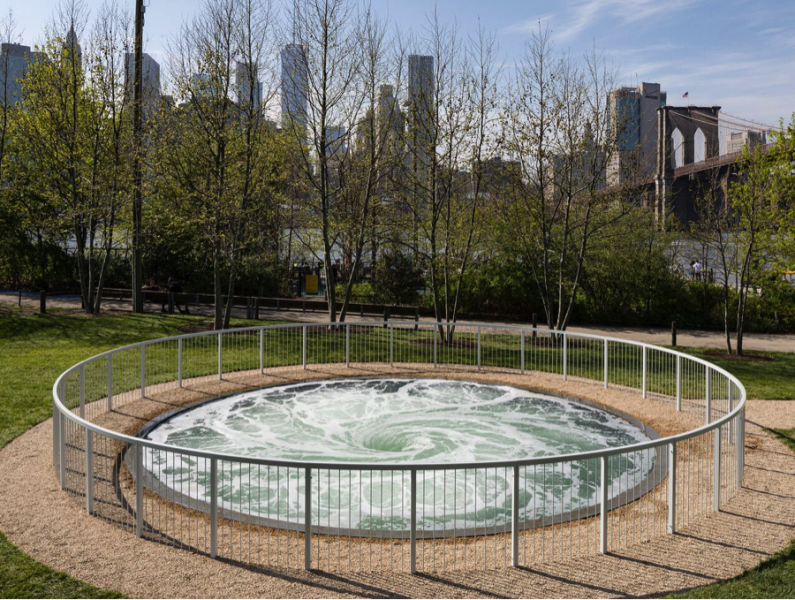 A large whirlpool by artist Anish Kapoor surrounded by a metal fence sits in a green area with the Brooklyn bridge behind it.