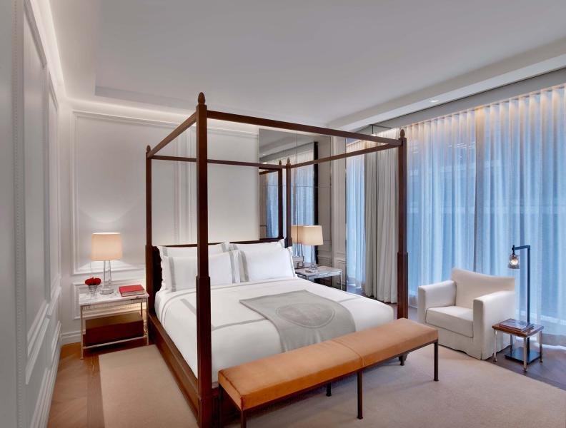 A four post king sized bed in a guest room at Baccarat hotel