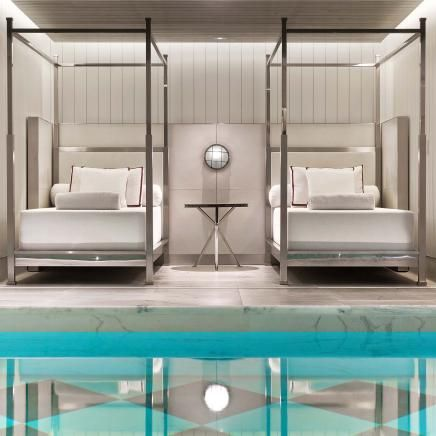 Two day beds by the side of an interior swimming pool