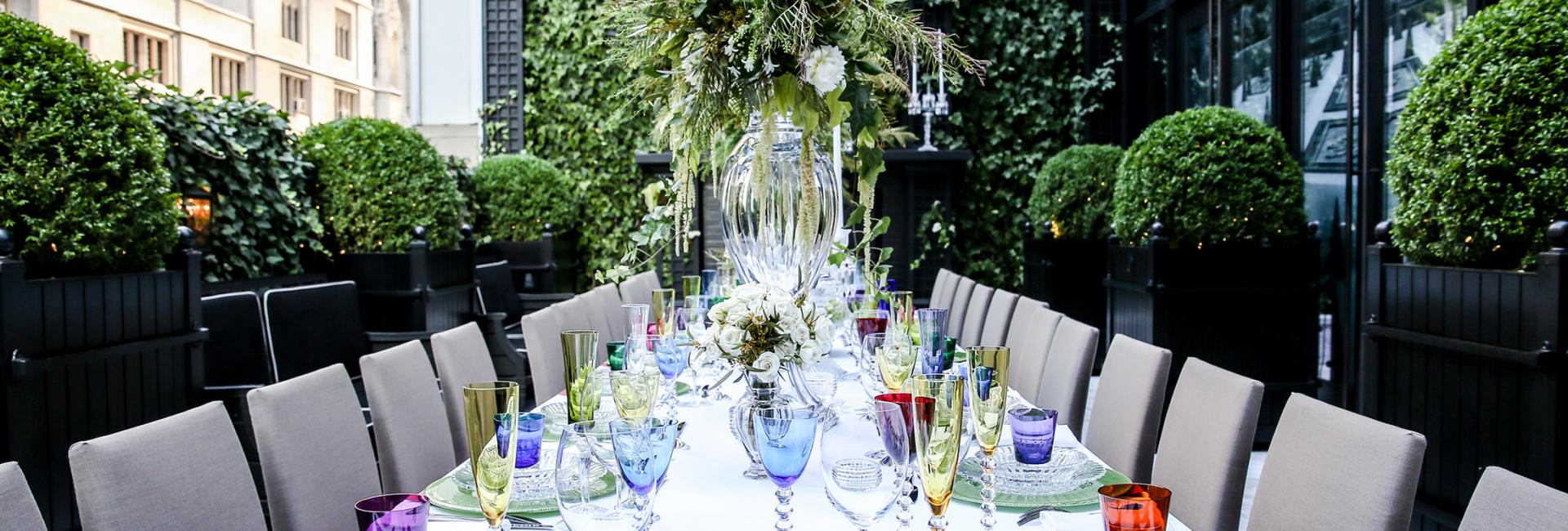 A long outdoor table set with colorful glassware and flowers