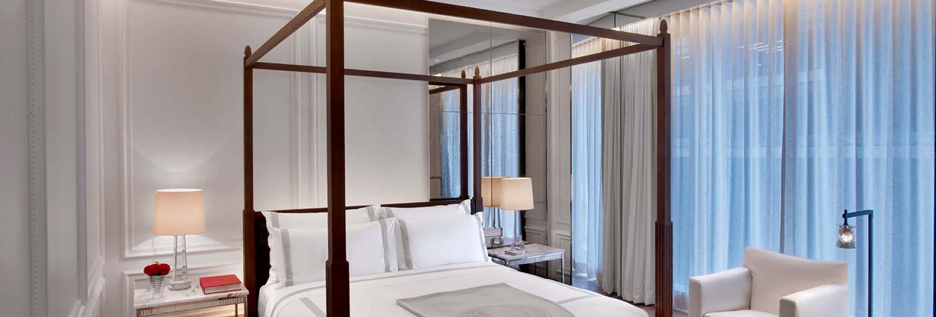 A white four post bed in the Prestige Suite of the Baccarat hotel